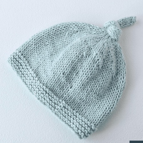Tegan Baby Knit Hat with Top Knot - Crochet and knitting are crafts that use knitting yarn and stitchwork to create garments and other projects. And both methods have loads of benefits. #crochet #knitting #knittingvscrochet