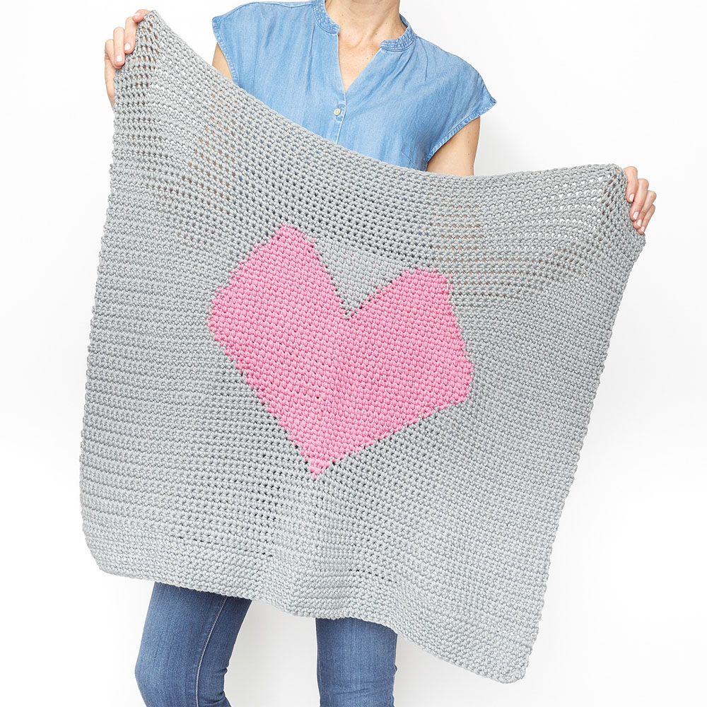 This easy baby blanket is fun to work on and full of love. This free crochet pattern would make a sweet gift for a family friend or even donate one to the local hospital. #CrochetBabyBlanket #EasyCrochetBabyBlanket #BabyBlanketPattern