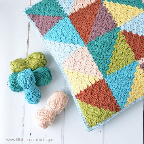 Pastel Triangles Pillow - This list of C2C crochet patterns will allow you make things you never dreamed of. Your friends will be impressed by your talent and you can make them gifts they could never buy in stores. #C2CCrochet #CornerToCornerCrochet #CrochetPatterns